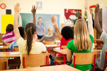 Rear view of the teens sitting in the classroom and raising hands to answer the question.  [url=http://www.istockphoto.com/search/lightbox/9786738][img]http://dl.dropbox.com/u/40117171/group.jpg[/img][/url]