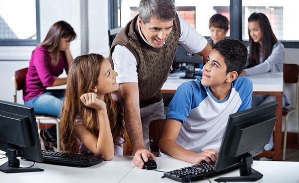 Teacher Using Computer With Students In Classroom